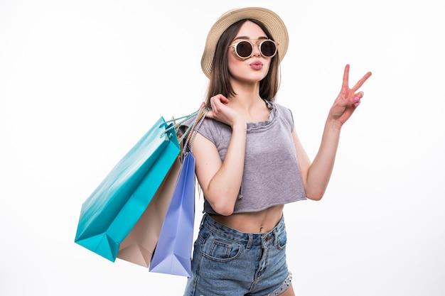 Полный портрет счастливой возбужденной девушки в яркой красочной одежде, держащей хозяйственные сумки, стоя и показывая жест мира изолированы Бесплатные Фотографии