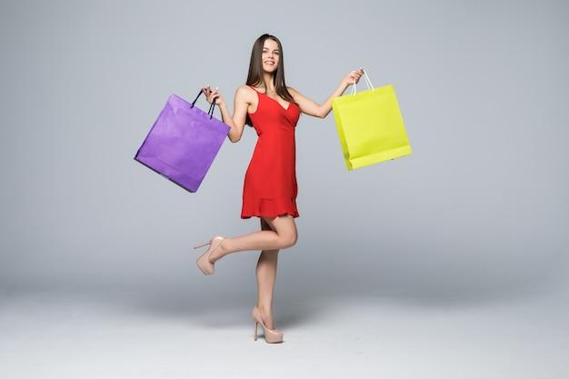白い壁に分離されたカラフルなショッピングバッグを立って保持している赤いドレスを着て幸せな興奮した女性の全身像 無料写真