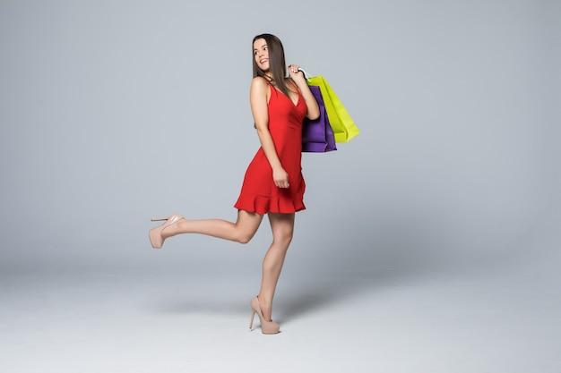 Полный портрет счастливой возбужденной женщины в красном платье, стоящей и держащей красочные хозяйственные сумки, изолированные на белой стене Бесплатные Фотографии