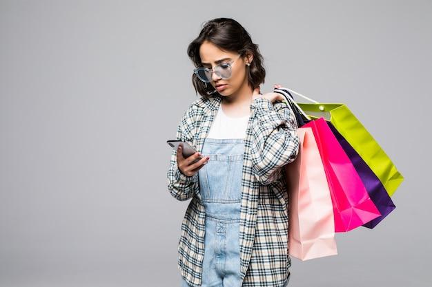 買い物袋と分離された携帯電話を保持している幸せな若い女性の完全な長さの肖像画 無料写真