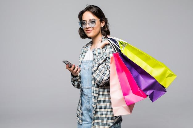 Портрет счастливой молодой женщины в полный рост, держащей сумки и мобильный телефон изолированы Бесплатные Фотографии