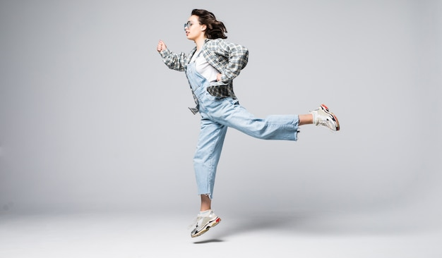 Портрет в полный рост радостной молодой женщины прыгает и празднует Бесплатные Фотографии