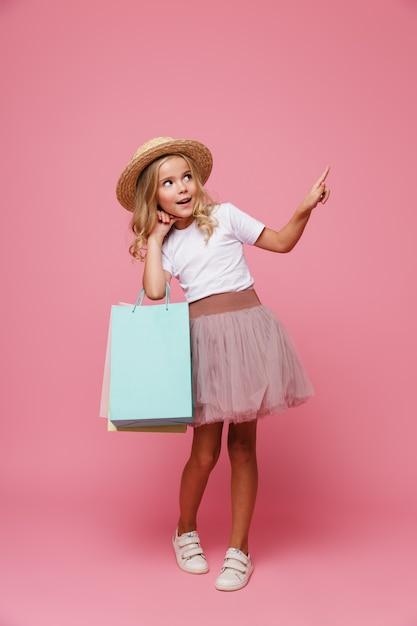 모자에 웃는 어린 소녀의 전체 길이 초상화 무료 사진