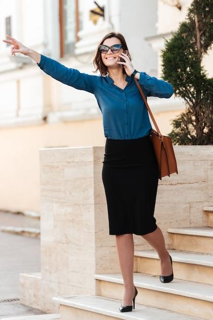 Полная длина портрет улыбающейся молодой женщины в солнцезащитных очках Бесплатные Фотографии