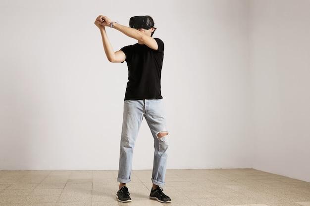 Портрет молодой кавказской модели в голубых рваных джинсах и черной футболке в полный рост, играющей в бейсбол или теннис в очках vr Бесплатные Фотографии