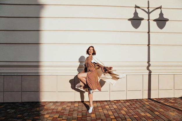 Полнометражный портрет активной девушки, танцующей в солнечный день. наружная фотография жизнерадостной кудрявой женщины, дурачащейся на улице. Бесплатные Фотографии