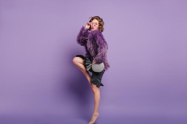 冬のジャケットの写真撮影中につま先で立っている裸足の女の子のフルレングスの肖像画 無料写真