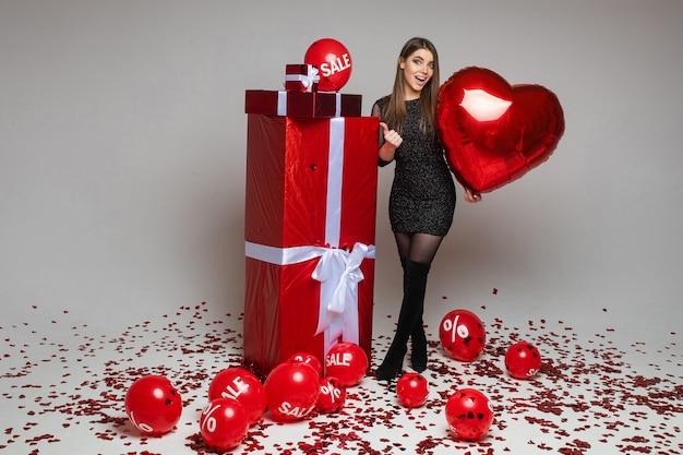 Полнометражный портрет девушки брюнетки кавказской с воздушным шаром в форме сердца, указывая большим пальцем на обернутые подарки. воздушные шары с распродажей и скидкой на полу с конфетти. Бесплатные Фотографии