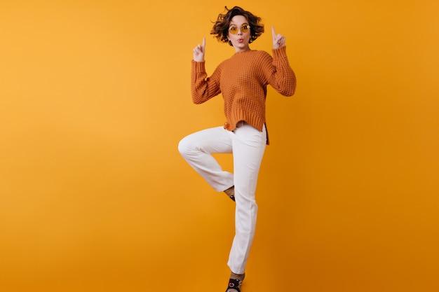 オレンジ色のスペースにジャンプする白いズボンの屈託のない女の子の全身像 無料写真