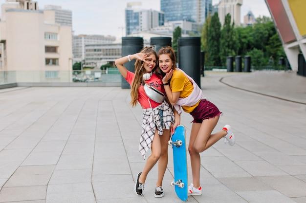 親友の横に青いスケートボードで片足に立っている陽気な面白い女の子の全身像 無料写真