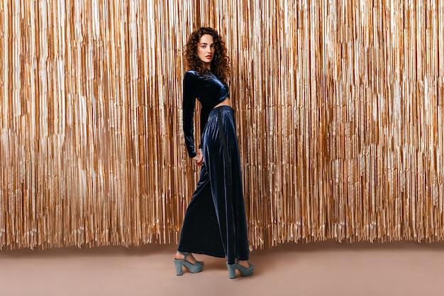 골드 배경에 벨벳 정장을 입고 곱슬 아가씨의 전체 길이 초상화 무료 사진