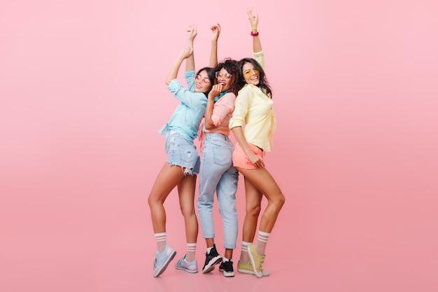 Полнометражный портрет милых девушек, стоящих с поднятыми руками и смеющихся с розовым интерьером. великолепная африканская дама позирует между международными друзьями в повседневной одежде. Бесплатные Фотографии