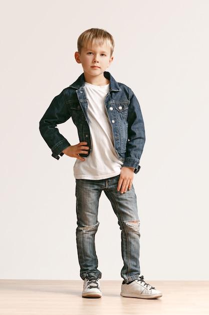 Полнометражный портрет милого маленького мальчика ребенка в стильной джинсовой одежде и усмехаясь, стоя на белизне. концепция детской моды Бесплатные Фотографии