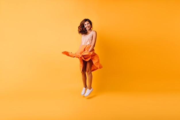 スタジオでジャンプするデボネアのスタイリッシュな女性の全身像。楽しんでいるオレンジ色のスカートのゴージャスな生姜の女の子。 無料写真