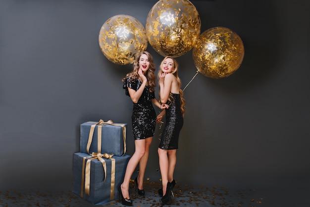 Полнометражный портрет мечтательной женской модели с вьющейся прической, держащей партийные воздушные шары в своей комнате. фотография в помещении довольной девушки в черном платье, стоящей возле синей подарочной коробки. Бесплатные Фотографии