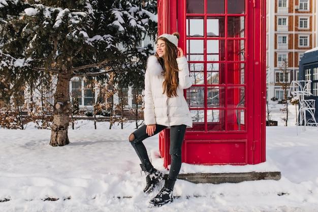 Портрет восторженной дамы с длинной прической в полный рост, позирующей возле красной телефонной будки зимой. фото красивой кавказской женщины в белой шляпе, наслаждающейся декабрьскими каникулами в англии. Бесплатные Фотографии