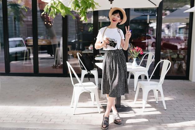 足を組んでピースサインと立っている黒いスカートと麦わら帽子で興奮したブルネットの若い女性の全身像 無料写真