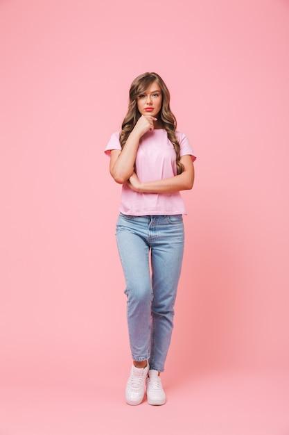 ピンクの背景に分離された真剣な表情で彼女のあごに触れるカジュアルな服を着ている長い巻き毛のヘアスタイルを持つ豪華なブルネットの女性20代の完全な長さの肖像画 Premium写真