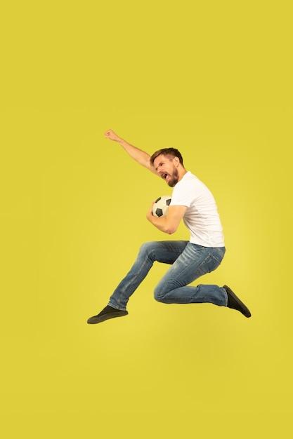 노란색 배경에 고립 행복 점프 남자의 전체 길이 초상화. 캐주얼 옷에 백인 남성 모델 무료 사진