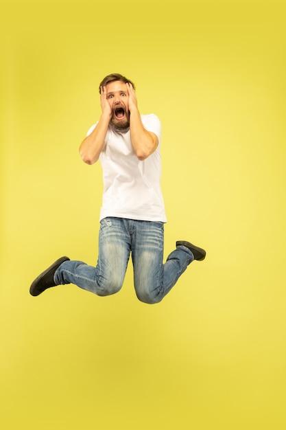 노란색에 고립 된 행복 점프 남자의 전체 길이 초상화 무료 사진