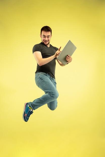 노란색 배경에 고립 된 가제트와 함께 행복 점프 남자의 전체 길이 초상화. 현대 기술, 선택의 자유 개념, 감정 개념. 비행 중 업무와 재미를 위해 노트북을 사용합니다. 무료 사진