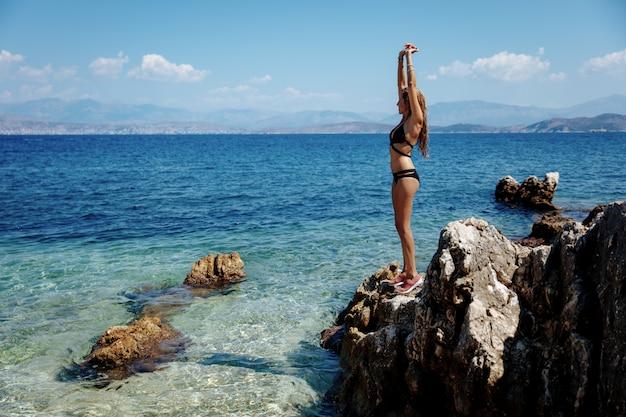 Полная длина портрет горячей девушки в бикини, охлаждение у моря Premium Фотографии