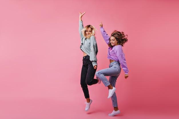 Полнометражный портрет прыгающих белых девушек, выражающих счастливые эмоции. портрет смешных танцев лучших друзей вместе. Бесплатные Фотографии