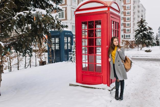 革のバッグが電話ボックスの近くに立って目をそらしている素敵なヨーロッパの女性の全身像。冬の日の電話ボックスの横にポーズグレーのコートを着た見事な白人女性の屋外写真。 無料写真