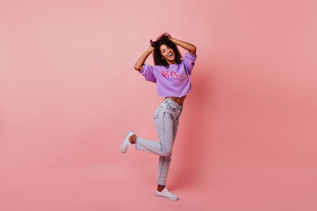 Полнометражный портрет оптимистичной смеющейся женщины, танцующей в студии. расслабленная фигурная женская модель наслаждается жизнью. Бесплатные Фотографии