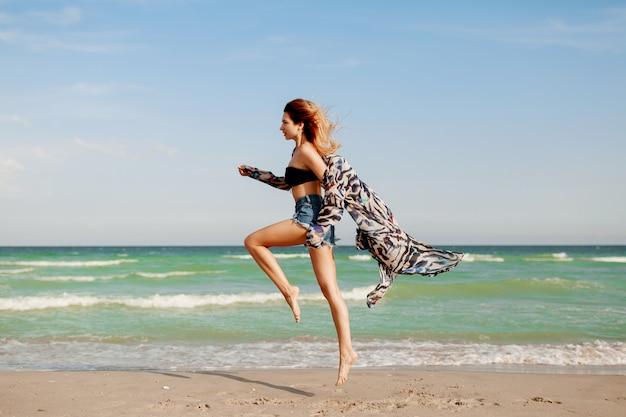 Полнометражный портрет довольно стройная девушка, наслаждаясь видом на горизонт на морском курорте. Бесплатные Фотографии