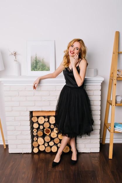 Портрет красивой молодой женщины в полный рост, разговаривает по телефону и улыбается в комнате с красивым и современным интерьером. в элегантном черном платье. Бесплатные Фотографии