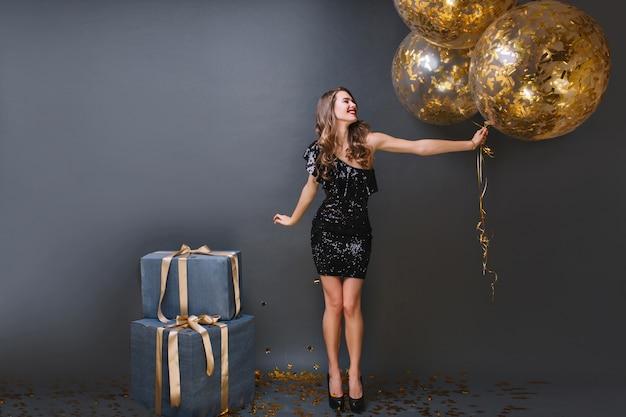 Портрет утонченной европейской девушки в черном платье на дне рождения в полный рост. блаженная длинноволосая дама с воздушными шарами не может дождаться открытия подарков. Бесплатные Фотографии