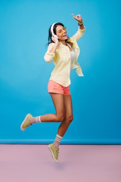 Портрет в полный рост утонченной латинской женщины с загорелой кожей, прыгающей и улыбающейся. изящная стройная девушка в модных носках носит большие белые наушники и слушает музыку. Бесплатные Фотографии