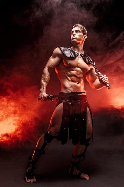 セクシーな若い戦士の剣を保持し、火に対してポーズをしながら離れて見ているのフルレングスの肖像画。 Premium写真