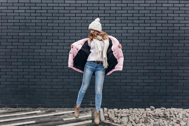 通りで踊るジーンズとピンクのジャケットのスリムな女の子の全身像。ポジティブな感情を表現するニット帽のゴージャスな女性モデルの屋外ショット。 無料写真