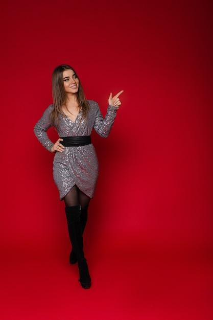 Полный портрет улыбающейся жизнерадостной девушки в коктейльном серебряном платье и черных высоких сапогах, указывающих на красную копию пространства. Бесплатные Фотографии
