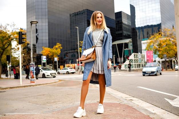 ビジネスセンターの建物の近くの通りでポーズ、ドレスコートとスニーカー、ファッションのライフスタイル、肯定的な気分を着てスタイリッシュなかなり陽気なブロンドの女性の完全な長さの肖像画。 無料写真