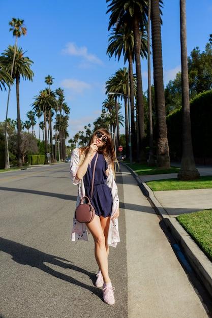 晴れた暑い日にホテル近くのエキゾチックな通りを歩いてスタイリッシュな笑顔の女性の完全な長さの肖像画。ロサンゼルスでの休暇を過ごす 無料写真
