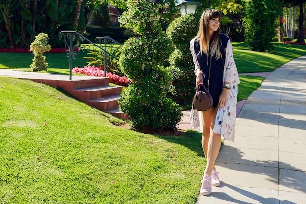晴れた暑い日にホテル近くのエキゾチックな通りを歩いてスタイリッシュな笑顔の女性の完全な長さの肖像画。ロサンゼルスでの休暇を過ごす。 無料写真