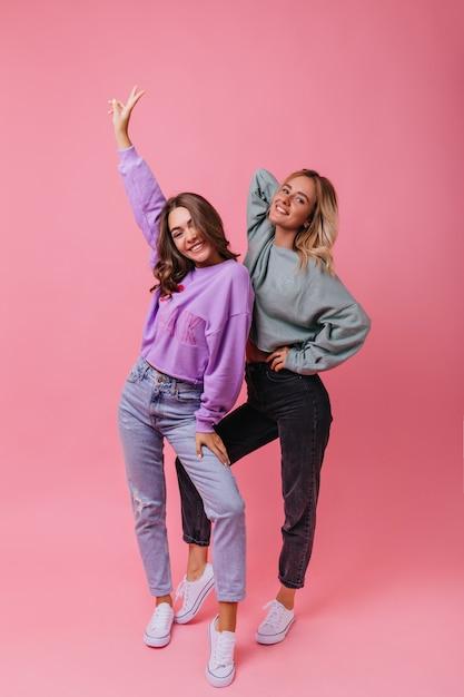Портрет чудесных девушек в винтажном уличном наряде в полный рост. кавказские модные дамы танцуют на розовом. Бесплатные Фотографии