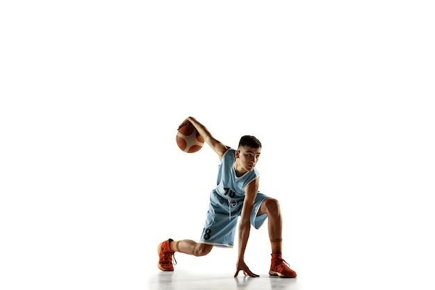 白いスタジオの背景に分離されたボールを持つ若いバスケットボール選手の全身像。 10代の若者のトレーニングと練習、アクション、モーション。スポーツ、動き、健康的なライフスタイル、広告の概念。 無料写真