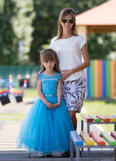 幼稚園のぼやけた遊び場でサングラスをかけた若いブロンドのスリムな笑顔の幸せな母親と長い青いイブニングドレスの小さなかわいい娘の女の子の全身像。 Premium写真