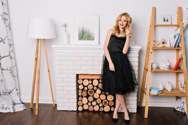 Портрет молодой блондинки в полный рост в светлой комнате с красивым современным интерьером, торшером, фальшивым камином, стеллажами с фигурками, книгами. в стильном черном платье и туфлях. Бесплатные Фотографии