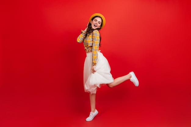 Full-length portrait of positive stylish lady jumping on red wall. woman in plaid shirt and white skirt is dancing in great mood. Free Photo
