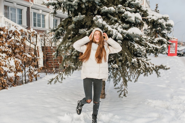 Full-length portrait of relaxed blonde woman in black pants dancing at snowy street with smile. outdoor photo of funny graceful woman posing with hands up in front of green spruce in winter day.. Free Photo