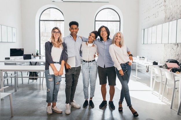 Full-length portrait of shy blonde woman in white sneakers holding laptop after seminar and stands beside african friend. excited international students posing together after lecture in spacious hall. Free Photo