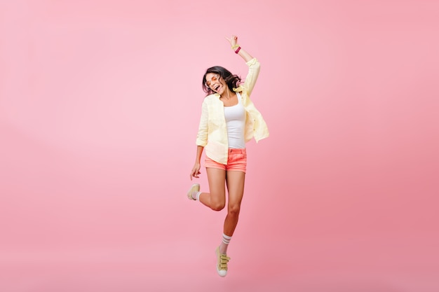 Full-length portrait of slim young woman with tanned skin jumping with smile. portrait of happy brunette girl in yellow shirt, dancing and singing with eyes closed. Free Photo