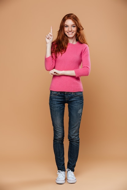 Full length portrait of a smiling young redhead girl pointing up with fingers Free Photo