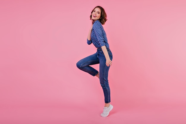 Full-length portrait of sporty girl with wavy hair. indoor shot of jumping young woman in jeans and blue shirt. Free Photo