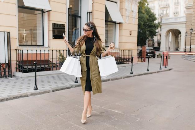 Ritratto a figura intera della splendida modella femminile che parla al telefono mentre trasporta borse per strada Foto Gratuite